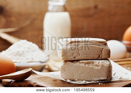 Fresh yeast and ingredients for baking on vintage kitchen background. Product for preparing pizza or bread.