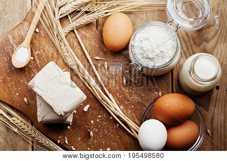 Fresh yeast and ingredients for baking on rustic kitchen table from above. Product for preparing pizza or bread.