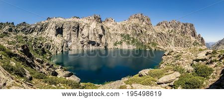 Dramatic rock formations surrounding the turquoise Lac de Capitello in the mountains above Restonica near Corte in Corsica