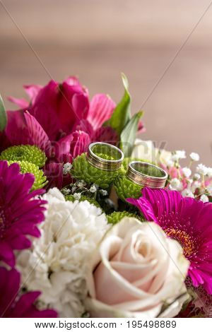 Two wedding rings on flowers of a bridal colorful bouquet with purple daisies white carnations and pale pink roses.