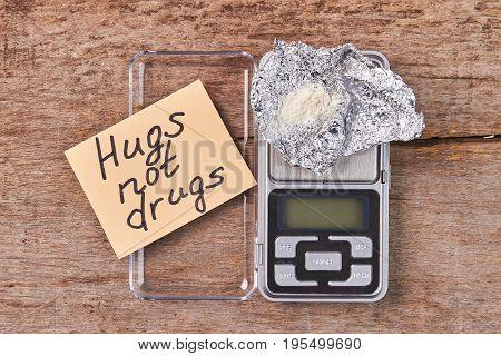 Paper message, digital scales, heroin. Hugs not drugs.