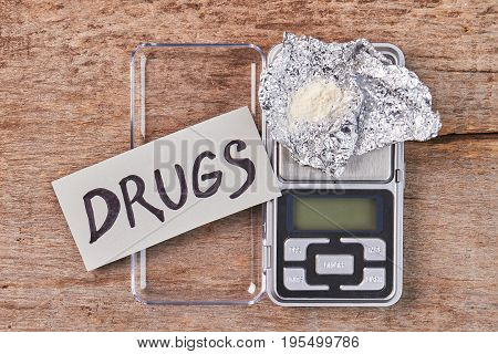Concept of drugs business. Close up of drugs, digital scales, white powder, message.