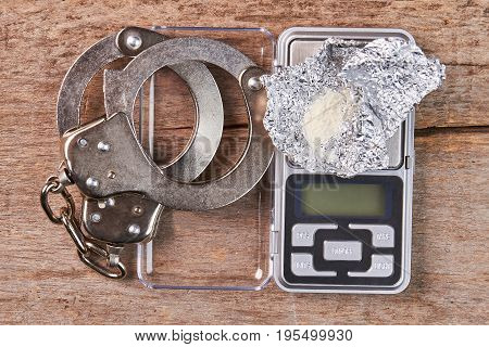 Handcuffs, digital scales, heroin close up. Punishment of narcotics dealers.