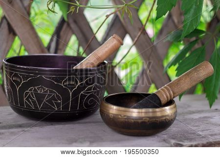 Wo Tibetan Singing Bowls With Sticks On A Wooden Bench In A Garden