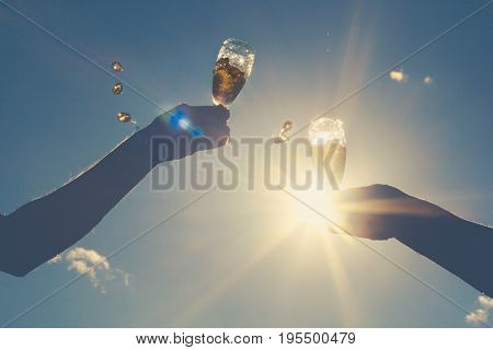 Hands Of Man And Woman Clink Wineglasses Of Sparkling White Wine On  Sky And Sun. Retro Toned