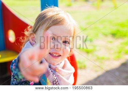 happy pretty child girl showing thumbs up.