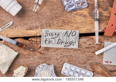 Say no to drugs today. Amount of narcotics, old wooden background.