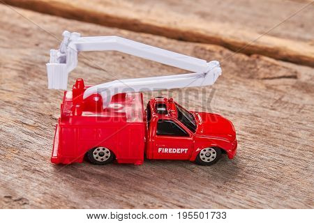 Red toy fire truck, wooden background. Model of fire lorry, old wooden floor.