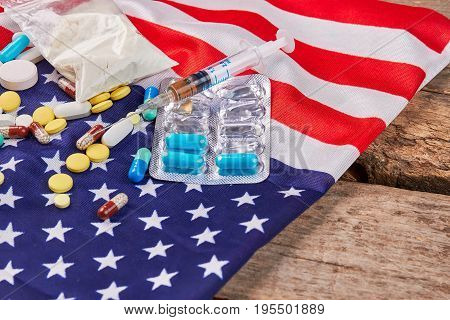 American flag, narcotics close up. Flag of America, syringe, pills, packet, wooden floor.
