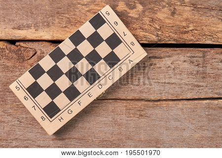 Folded checker board, top view. Closed box with checkers on old wooden background.