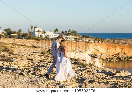 Beautiful young couple holding hands on the beach.