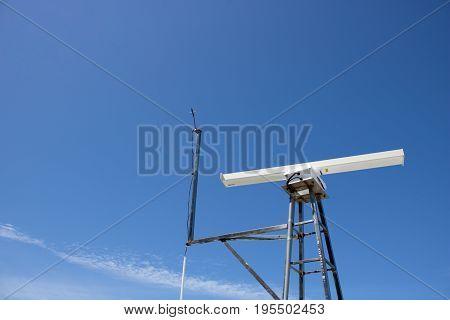 electronic equipment mast on coast against blue sky