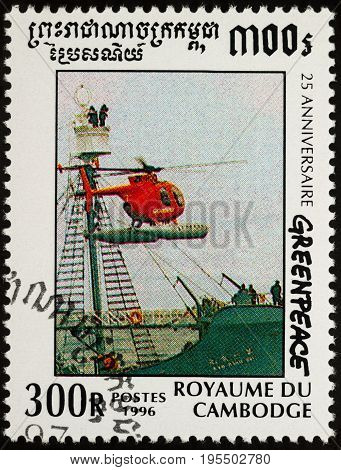 Moscow Russia - July 15 2017: A stamp printed in Cambodia shows red helicopter hovering over the green ship series