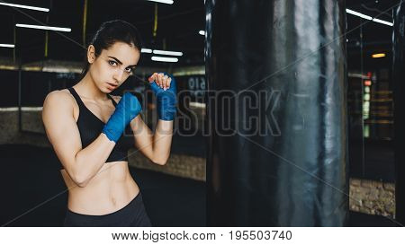 Pretty young woman wearing sports costume posing in combat stance looking at camera. Fit young female boxer ready for fight on dark gym background. Close up