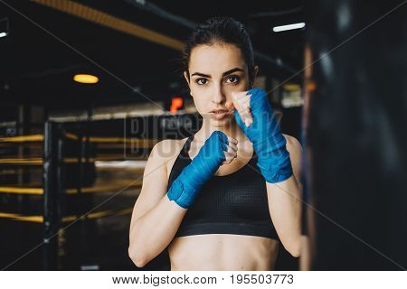 Attractive woman in sportswear posing in combat stance with warpped hands. She has warming up before the training in the gym. Close up