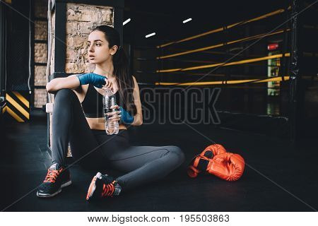 Tired sportive girl sitting in the gym near the window and looking at it. Young woman is thirsty so she is opening bottle with water.