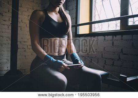 Young sportive and slim woman having some rest after hard workout in gym. She is sitting in the gym near the window and watching a video. Close up