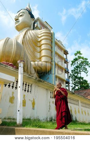 Dickwella Sri Lanka 04-15-2017: A Buddhist monk holds a mobile phone in the hands of a Buddhist temple on the background of a Buddha statue
