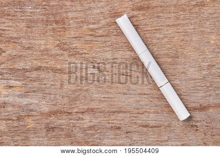 White tobacco cigarette on wooden background. Cigarette addiction leads to cancer of lungs.