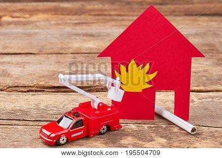 Toy fire truck, flaming building, wooden background. Smoking cigarettes make a fire in the house.
