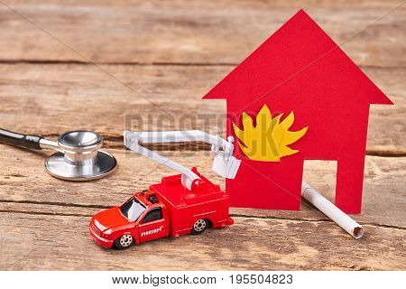 Burn cigarette caused the fire. Stethoscope, toy flaming building, toy fire truck, cigarette, wooden background. Do not play with fire.