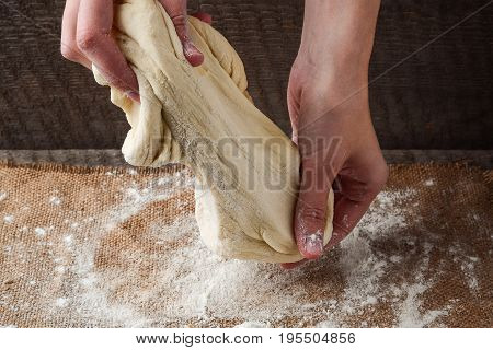 Female hands prepare dough for pizza on a dark background