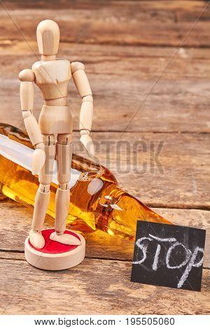 Human wooden model, bottle, message. Stop alcoholism concept.
