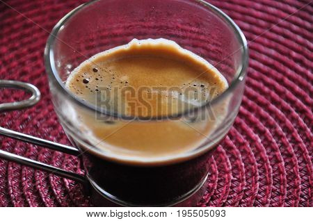 A shot of espresso on a lined red background