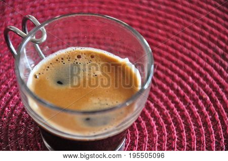A photo of a shot of espresso on a red lined background