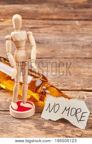 Human model dummy, alcohol, message. No more alcohol text, wooden human figurine, wooden background.