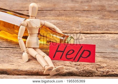 Stop drinking message, wooden dummy. Wooden puppet, transparent bottle, wooden background.