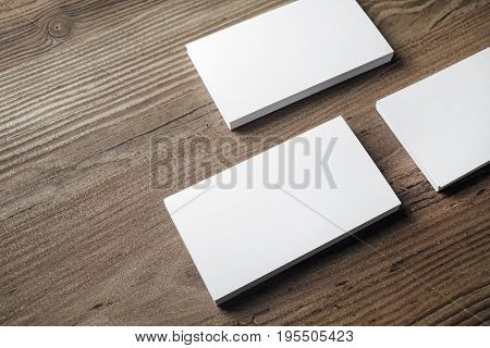 Blank white business cards on wood background. Mock-up for branding identity. Blank template for placing your design. ID mock up.