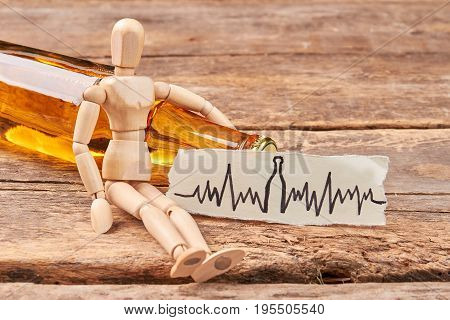 Human wooden figurine, alcohol beverage. Wooden dummy, image of heart beat, wooden background.