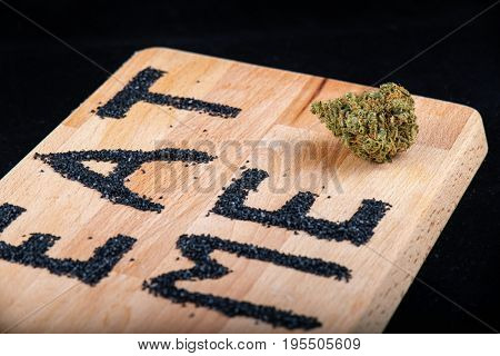 Single cannabis bud on a wooden surface with the words
