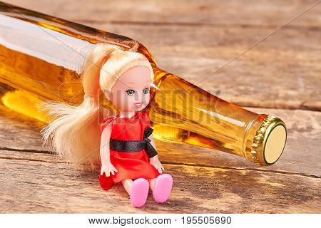 Toy doll sitting with alcohol. Toy, bottle of beer, wooden background. Metaphor concept of alcohol addiction.