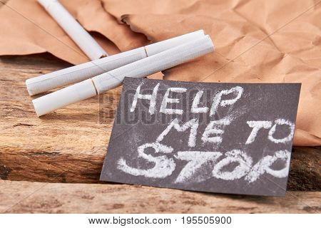 Nicotine is dangerous for life. Vintage burnt paper, cigarettes, message. Help to stop nicotine addiction.