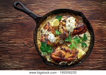 Creamy chicken fellets supremes in mushroom sauce with parsley In rustic cast iron skillet