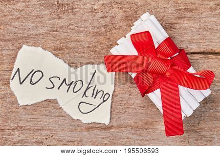 Pile of tobacco cigarettes and red bow. Message no smoking, cigarettes wrapped in red ribbon as gift.