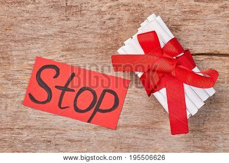 Pile of cigarettes with bow as gift. Message stop, cigarettes with filter and red ribbon, wooden background.