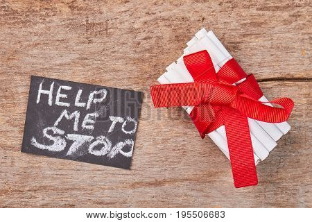 How to stop for nicotine addictive. Message with text help to stop, pile of tobacco cigarettes with red ribbon and bow, wooden background.