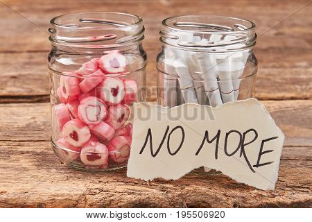 Sweets, cigarettes, note, glass jars. No more unhealthy lifestyle and bad habits concept.