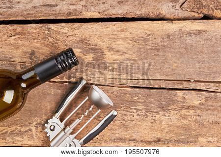 Corkscrew and wine bottle on wooden background. Bottle of alcoholic drink and opener lying on old wooden background.