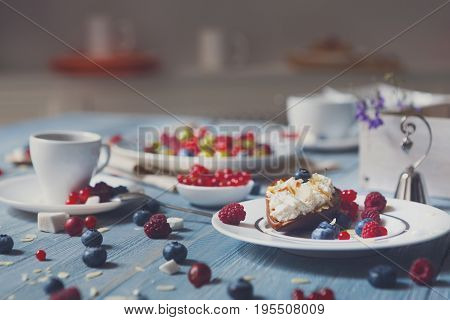 Sweet breakfast with baked pea and mascarpone dessert and berries - red currant, raspberry and bluberries. Beautiful food served at blue rustic wooden table, dish at white porcelain plate, coffee cup.