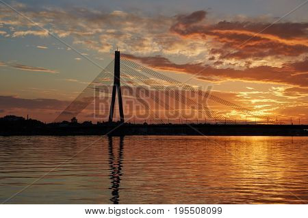 Silhouette of a cable-stayed bridge in Riga against a beautiful sunset