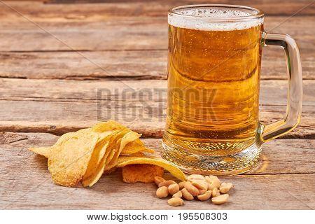 Potato chips, peanuts, glass of beer. Beer still life.