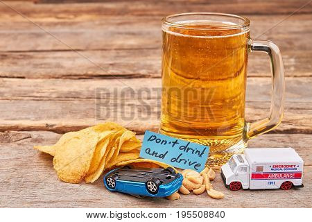 Glass of beer, turned over car, ambulance. Drink and drive dangerous for life.