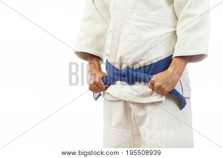 Close-up Of A Man  In A White Kimono For Judo, Ties Up A Blue Belt