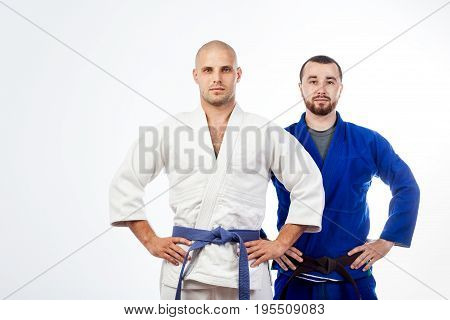 Two young men in a blue and white kimono for judo jujitsu posing on isolated white background
