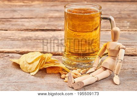 Human wooden dummy and beer. Concept of beer addiction. poster
