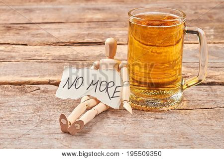 No more alcohol drinking concept. Male wooden figure, message, glass of beer, wooden background.